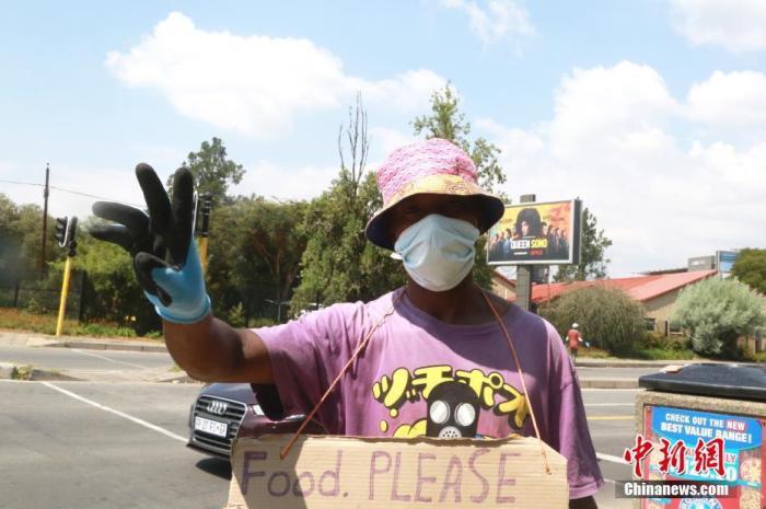 """当地时间4日1日,南非约翰内斯堡,一名街头艺人佩戴防护口罩、手套。受疫情影响,南非已经实施全国范围""""封城""""。 <a target='_blank' href='http://www.chinanews.com/'>中新社</a>记者 王曦 摄"""