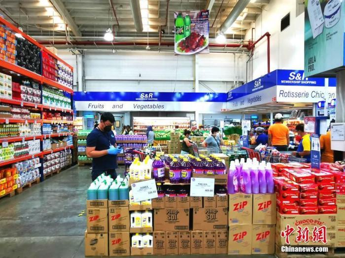 """4月1日,菲律宾首都马尼拉超市保障供应,货品充足,价格基本平稳。采购者付款时保持""""社交距离""""。 <a target='_blank' href='http://www.chinanews.com/'>中新社</a>记者 关向东 摄"""