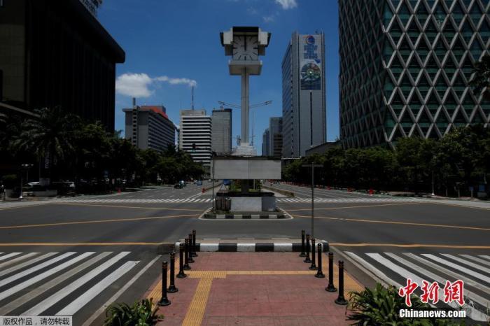 印度尼西亚雅加达主要道路正午时车辆稀少的十字路口。