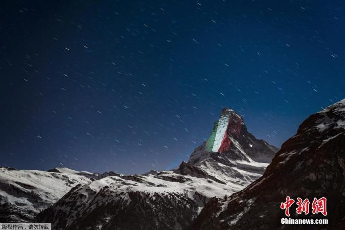 """当地时间4月1日,瑞士阿尔卑斯山脉标志性的马特洪峰显现灯光投影的庞大横幅,在疫情中呼吁""""期待和团结""""。图为灯光在马特洪峰山顶映出意大利国旗。"""