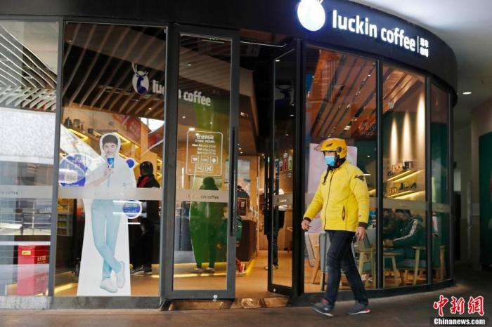 资料图:图为外卖小哥正前往店铺拿取咖啡。 殷立勤 摄