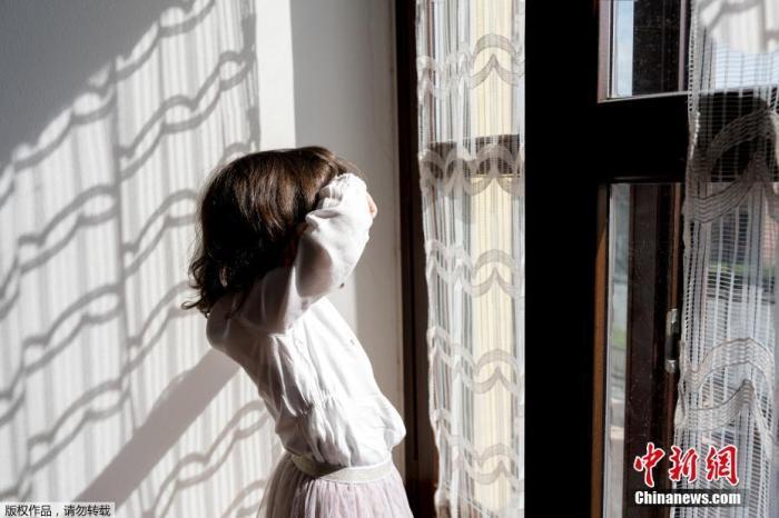 """资料图:意大利3月初宣布全国""""封城"""",原定4月3日解禁。大部分商铺、酒吧和餐馆关闭,民众除有必要不得离家。图为两岁的女儿比安卡晒着太阳望向窗外。"""