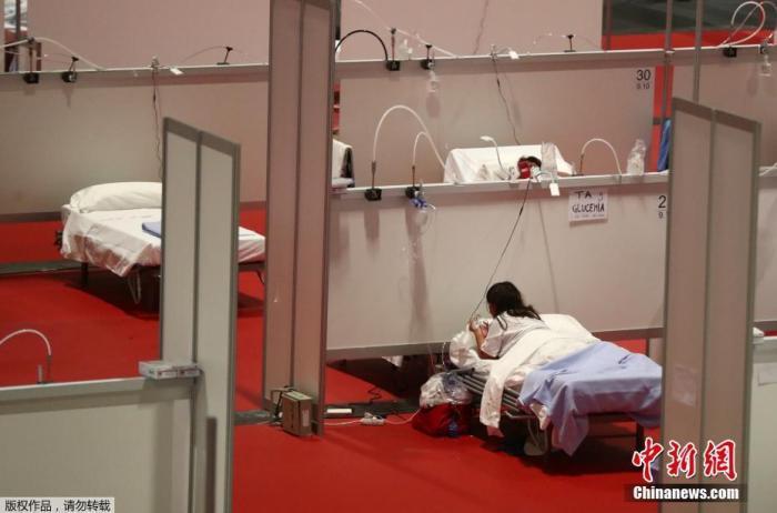 """当地时间4月2日,西班牙马德里会展中心""""方舱医院""""内,患者在接受治疗。"""