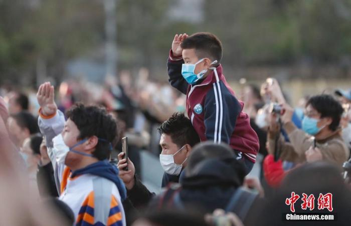 4月4日,北京天安门广场降下半旗,表达对抗击新冠肺炎疫情斗争牺牲烈士和逝世同胞的深切哀悼。图为参加升旗仪式的民众。 中新社记者 杜洋 摄