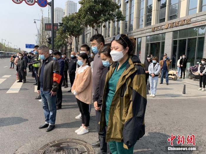 4月4日,武汉市防空警报鸣响,汽车停车鸣笛,民众在街头肃立默哀。当日,武汉市举行哀悼活动,表达对抗击新冠肺炎疫情斗争牺牲烈士和逝世同胞的深切哀悼。 中新社记者 杨程晨 摄