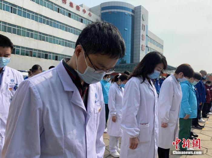 4月4日,武汉协和医院西院的医护人员肃立默哀。当日,武汉市举行哀悼活动,表达对抗击新冠肺炎疫情斗争牺牲烈士和逝世同胞的深切哀悼。 中新社记者 武一力 摄