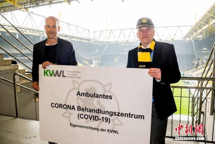 """4月3日,德甲多特蒙德俱乐部宣布,从4日起在其主场西格纳伊杜纳公园球场设立""""治疗中心"""",用于新冠病毒疑似患者的检测和确诊病例分诊。西格纳伊杜纳公园球场可容纳8.1万球迷,是德国最大的足球比赛场馆。图为多特总经理卡斯滕·克拉默和威斯特法伦-利珀公立医师协会第一主席斯培迈尔宣布此项合作。 <a target='_blank' href='http://www.chinanews.com/'>中新社</a>发 多特蒙德足球俱乐部 供图"""