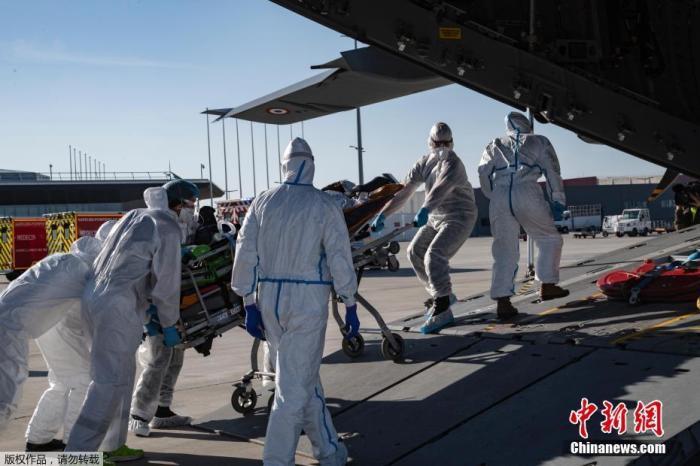 当地时间4月4日,法国奥利机场,医护人员将患者送上运输机。据法新社报道,奥利机场目前已对旅客关闭,变成一个疏散中心用于缓解巴黎地区医院的压力。