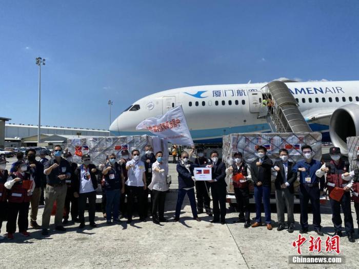 4月5日,中国政府赴菲律宾抗疫医疗专家组一行12人,乘坐由厦门航空执飞的包机抵达菲律宾首都马尼拉。图为中国驻菲律宾大使黄溪连(右六)和菲律宾外长洛钦(右七)出席在机场举行的物资交接仪式。中新社发 中国驻菲律宾使馆 供图