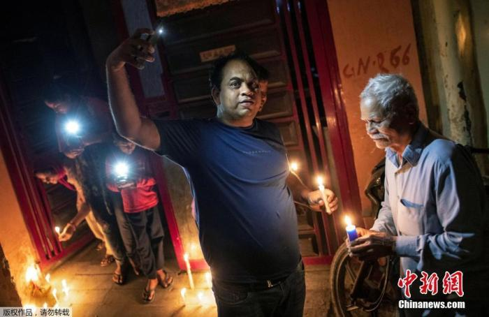 当地时间4月5日21点,印度民众熄灯9分钟,点燃蜡烛和油灯为抗疫祈福。图为新德里居民点燃蜡烛并且打开手机的手电筒。