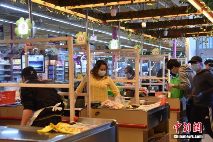 资料图:当地时间4月6日,美国大华府地区的一家超市在结账区收银员和顾客之间设置玻璃隔断,防止互相传染。 中新社记者 沙晗汀 摄