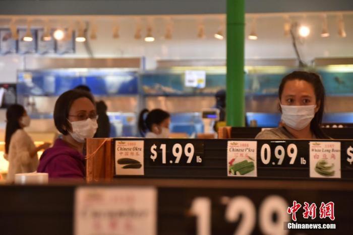 当地时间4月6日,在位于大华府地区的一家超市里,民多远大佩戴口罩购物。 中新社记者 沙晗汀 摄