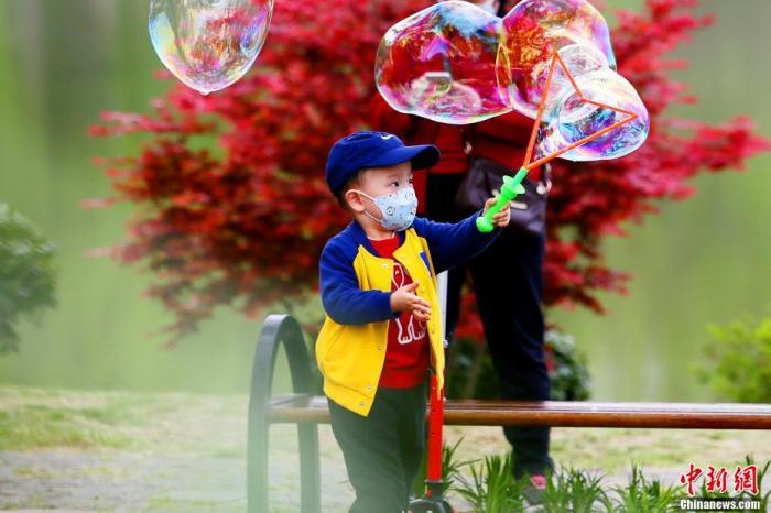 资料图:逐渐恢复活力的武汉,小男孩在东湖边开心玩耍。 王康荣 摄