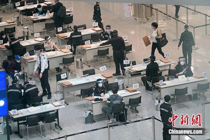 4月7日,工作人员在香港国际机场禁区为入境者办理居家检疫手续,并为入境者佩戴用于居家检疫监察的蓝牙电子手环。 中新社记者 张炜 摄