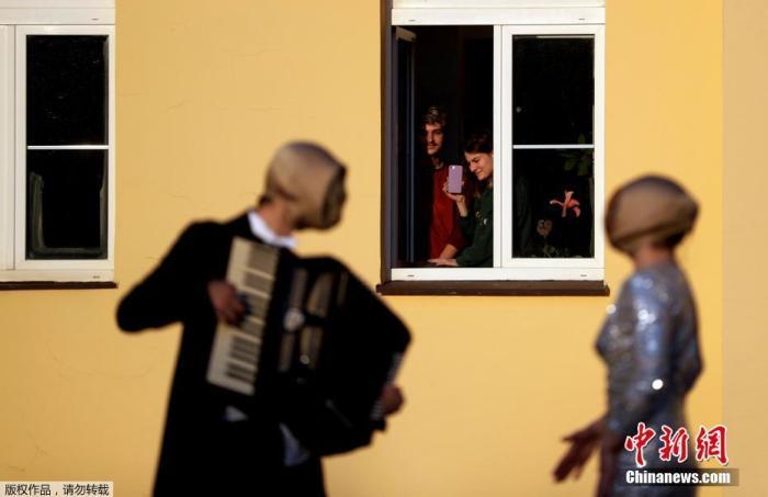 当地时间2020年4月7日,捷克共和国布拉格,街头音乐人在居民区表演,民众在窗前欣赏。