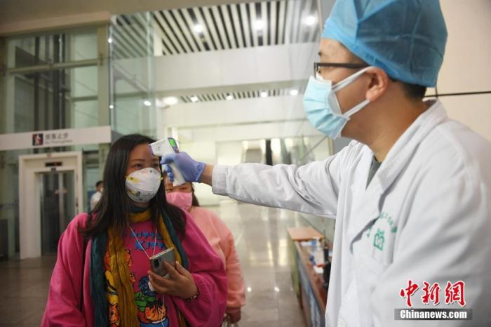 资料图:图为广州南站工作人员为旅客测温。 中新社记者 姬东 摄