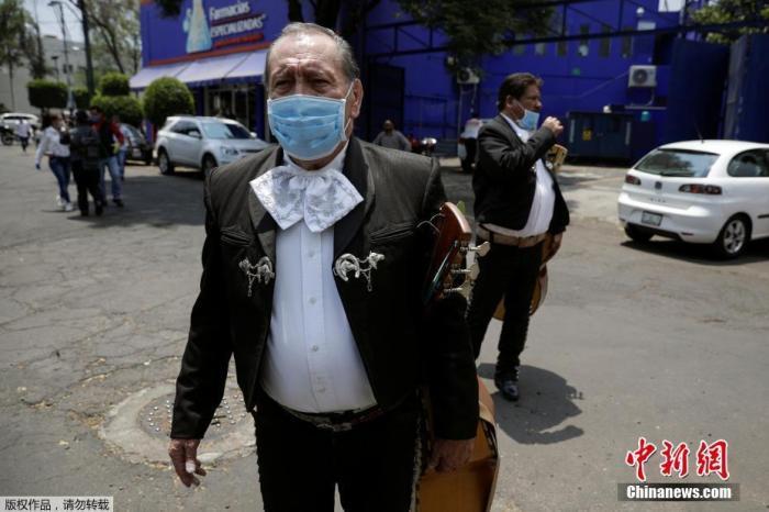 资料图:当地时间4月7日,墨西哥首都墨西哥城,一支流浪乐队戴上口罩着正装在街头为医护人员演奏小夜曲。