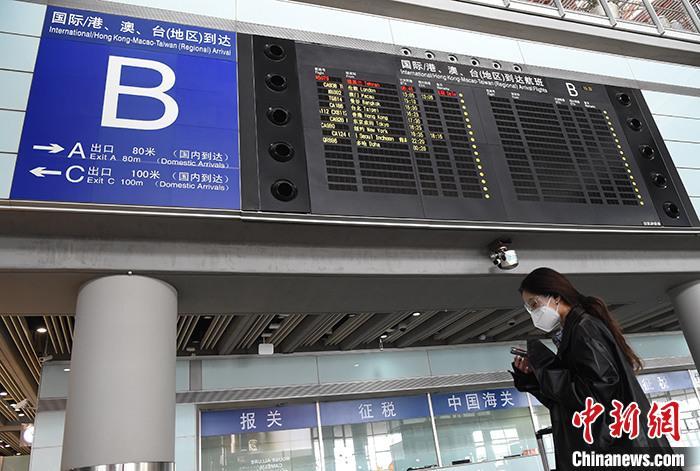 資料圖:4月8日,北京首都機場3號航站樓,一名女子經過到達航班信息屏。<a target='_blank' href='http://www.769358.buzz/'>中新社</a>記者 侯宇 攝