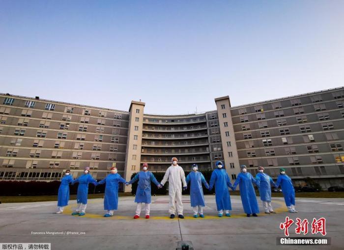 当地时间4月6日,意大利克雷莫纳一家医院的医务人员手牵手,向在新冠肺热疫情中受影响的人们外示声援和致意。