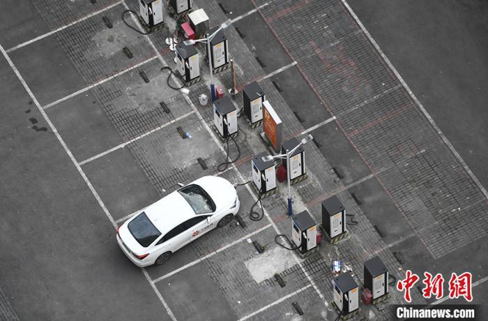 4月9日,重庆大渡口一停车场内,一新能源车辆正在充电桩处进行充电。 中新社记者 陈超 摄