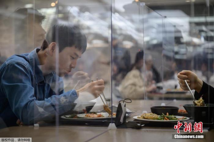 當地時間4月9日,位于韓國首爾的一家公司員工正在用餐,該公司為了保證員工的就餐安全,在自助餐區設置了玻璃罩。