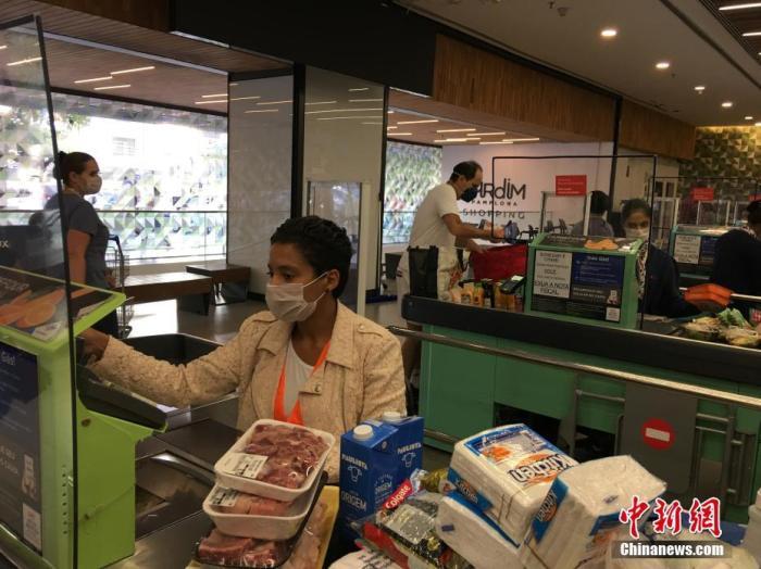 内地时间4月9日,在巴西圣保罗,一名戴着口罩的收款员在一家超市事情。