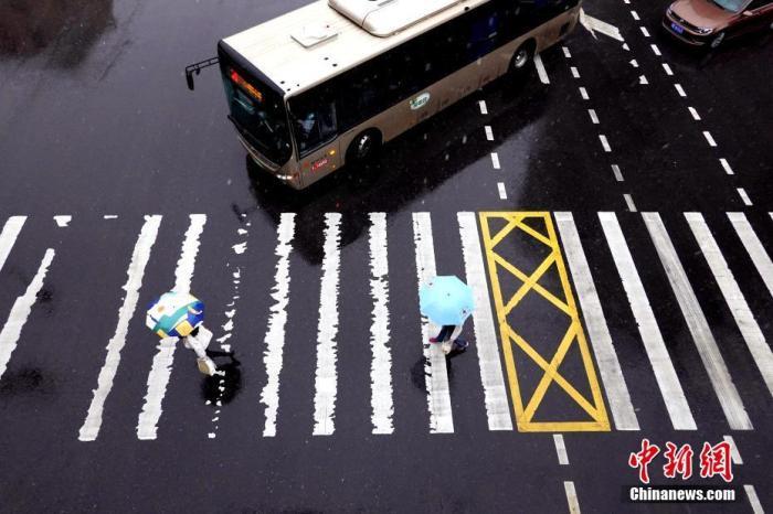 资料图:市民在雨中出行。<a target='_blank' href='http://vjdu.cn/'>中新社</a>记者 王中举 摄