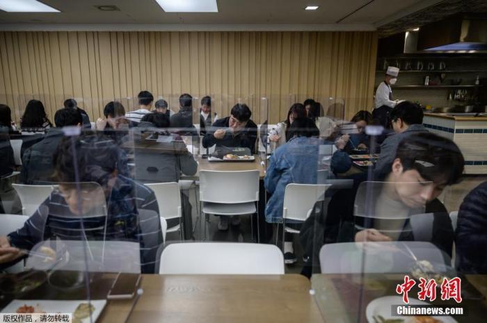 当地时间4月9日,位于韩国首尔的一家公司员工正在用餐,该公司为了保证员工的就餐安全,在自助餐区设置了玻璃罩。