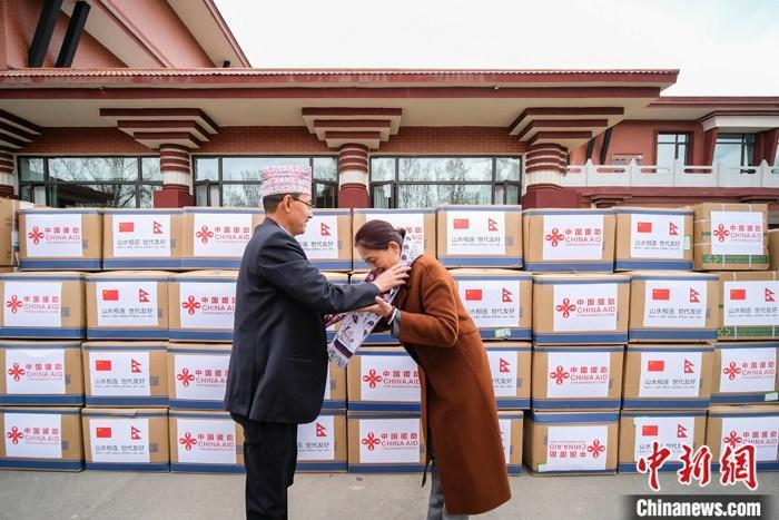 4月10日,中国西藏自治区政府援助尼泊尔抗疫医疗物资交接仪式在拉萨举行。据悉,此次捐赠的医疗物资包括新冠病毒检测仪器、核酸检测试剂盒、病毒采样管、医用防护服、N95口罩等。图为交接仪式结束后,尼泊尔驻拉萨总领事戈宾达・巴哈杜尔・卡尔基(左)向西藏自治区外事办公室主任白曼央宗献哈达。 中新社记者 何蓬磊 摄