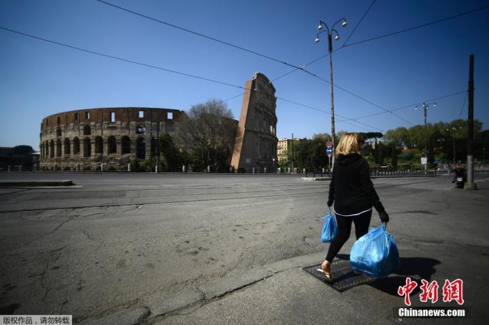 """当地时间4月10日,一名妇女背着垃圾袋穿过罗马体育馆纪念碑附近。意大利累计新冠确诊病例10日增至147577例,死亡病例18849例,治愈病例30455例。意总理孔特当天表示,原定4月13日结束的全国""""封城""""措施将延长到5月3日。"""