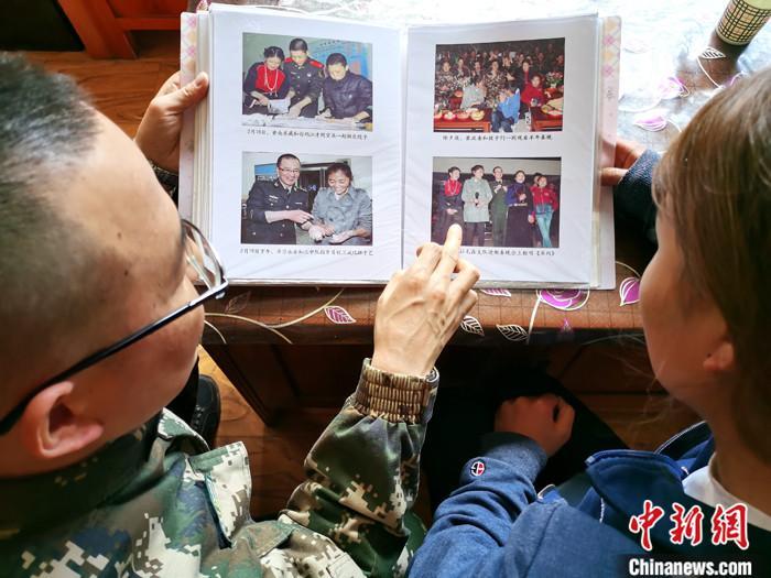 4月11日,武警青海总队玉树支队官兵到藏族女生才文拉毛家回访,翻看此前包括才文拉毛和弟弟在内的十名孤儿与武警官兵相处的照片。 记者 张添福 摄