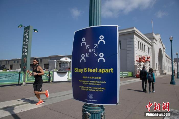 """当地时间4月12日,挑醒人们保持""""社交距离""""的标识张贴在美国旧金山海边一条步道旁。针对新冠肺热疫情的出走禁令颁布之后,这边比日常冷清了很多。 中新社记者 刘关关 摄"""