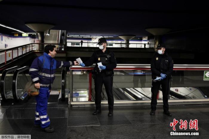当地时间4月13日,西班牙马德里,警察在地铁站向民众分发免费的防护口罩。