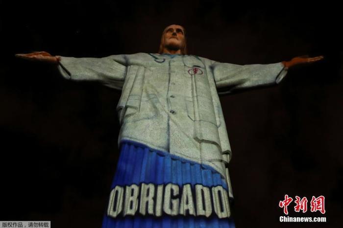 """当地时间4月12日,巴西里约热内卢的耶稣雕像穿上了""""白大褂"""",雕塑上用多国语言向在抗击新冠肺炎一线工作的医护人员表示感谢。"""
