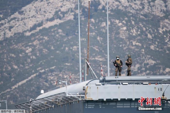 """当地时间4月12日,法国海军航空母舰""""戴高乐""""号当天返回法国土伦军港,航母编队1900多人须接受新冠病毒测试并被隔离。图为航母上的士兵带着口罩站在甲板上。"""
