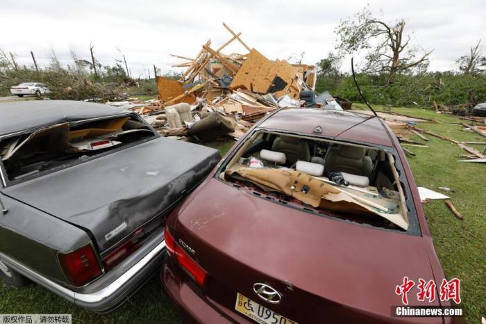 资料图:美国密西西比州巴斯菲尔德附近,龙卷风过后,两辆受损的汽车挤在一起。