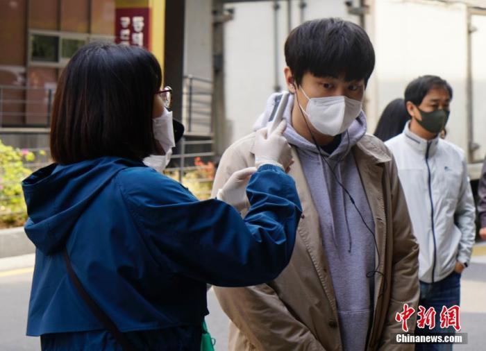 在韩国首尔一投票站,投票者接受体温检测。 <a target='_blank' href='http://www.chinanews.com/'>中新社</a>记者 曾鼐 摄