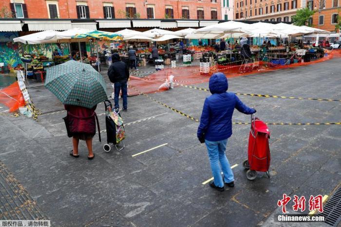 当地时间4月14日,意大利罗马,消费者在特拉斯蒂夫市场排队等候购买物资。为阻止新型冠状病毒的传播当地对露天市场实施了新的限制措施。