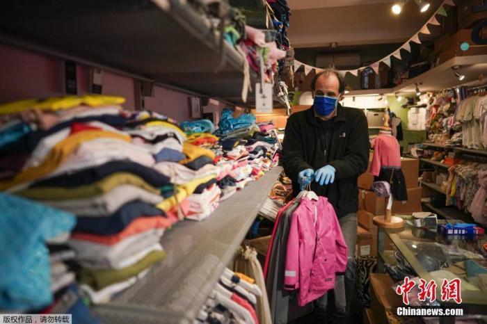 當地時間4月14日,意大利羅馬,Gianfranco Mandas在他的童裝店整理衣服準備營業。