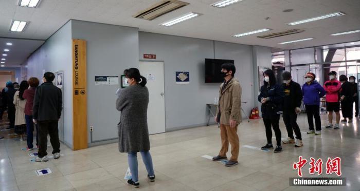 """当地时间4月15日,韩国在疫情""""红色预警""""中启动第21届国会选举。图为在韩国首尔一投票站,民众保持距离,排队等候投票。<a target='_blank' href='http://www.chinanews.com/'>中新社</a>记者 曾鼐 摄"""