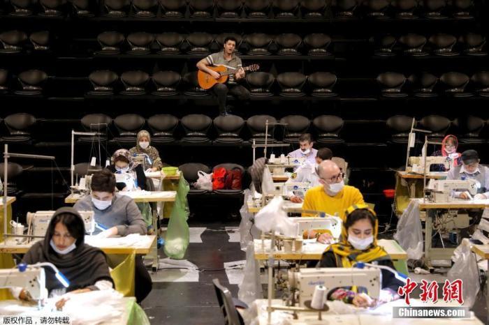 内地时间4月15日,伊朗德黑兰市中心的哈菲兹剧院大厅,一名吉他手给正在为抗击新冠肺炎疫情赶制口罩得志愿者们弹奏歌曲。
