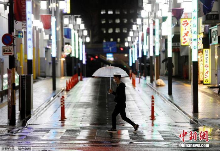"""当地时间4月16日晚,日本首相安倍晋三正式宣布,将""""紧急事态宣言""""适用范围扩展至日本全境,持续时间至5月6日。截至目前,日本境内新冠肺炎病例已超过9000例,东京都单日新增149例,冲绳出现首例死亡病例。日本将从17日起在全国范围内发放布口罩。图为日本东京一名男子戴着口罩在空旷的街头冒雨前行。"""