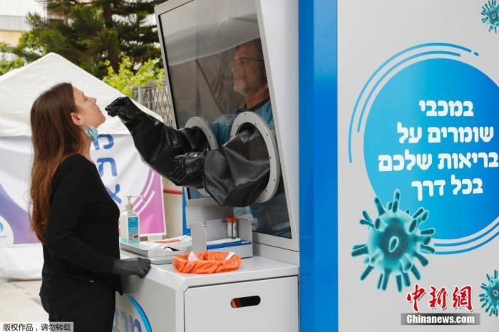 资料图:当地时间4月16日,以色列Maccabi医疗服务公司在沿海城市特拉维夫安装了一个新型冠状病毒测试台,医务人员可以从民众身上采集拭子样本。