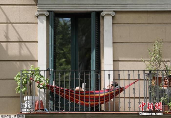 内地时间4月10日,西班牙巴塞罗那,住民在阳台上享受晴天气。