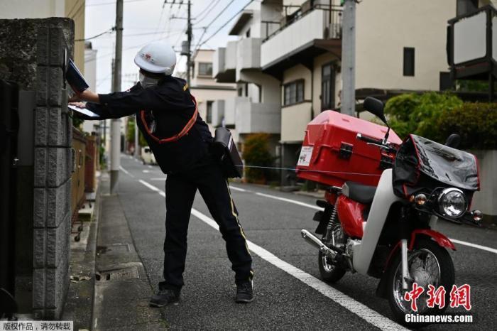 当地时间4月17日,东京一名邮政员工正在向居民派发免费口罩。此前,日本政府做出承诺,向日本每个家庭派发两个可重复使用的布口罩。