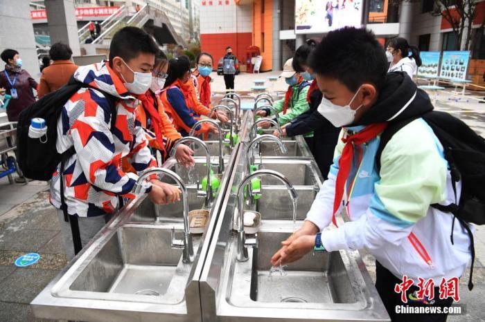 资料图:学生在校门口设立的洗手平台前洗手后进入校园。中新社记者 杨艳敏 摄