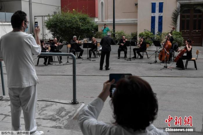 当地时间4月20日,新冠肺炎疫情期间,希腊雅典福音医院的医务人员在院子里聆听希腊国家广播交响乐团的音乐会。
