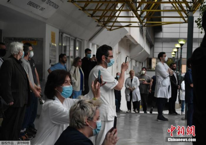 当地时间4月20日,新冠疫情期间,希腊雅典福音医院的医务人员在院子里聆听希腊国家广播交响乐团的音乐会。据悉,举办这次音乐会是为了感谢医院工作人员和所有卫生工作者在新冠肺炎疫情爆发期间所做的努力。图为医护人员在欣赏表演。
