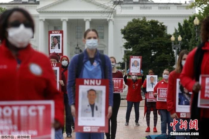 当地时间4月21日,美国华盛顿,美国最大的护士工会部分成员手举已感染新冠肺炎的同事照片,在白宫前呼吁政府加大力度投入生产防护设备。