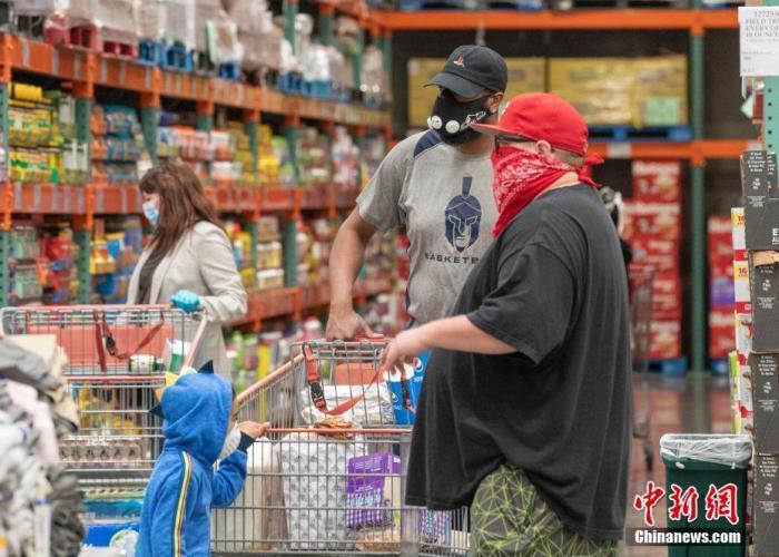 当地时间4月22日,顾客佩戴口罩或手帕购物。中新社记者 刘关关 摄
